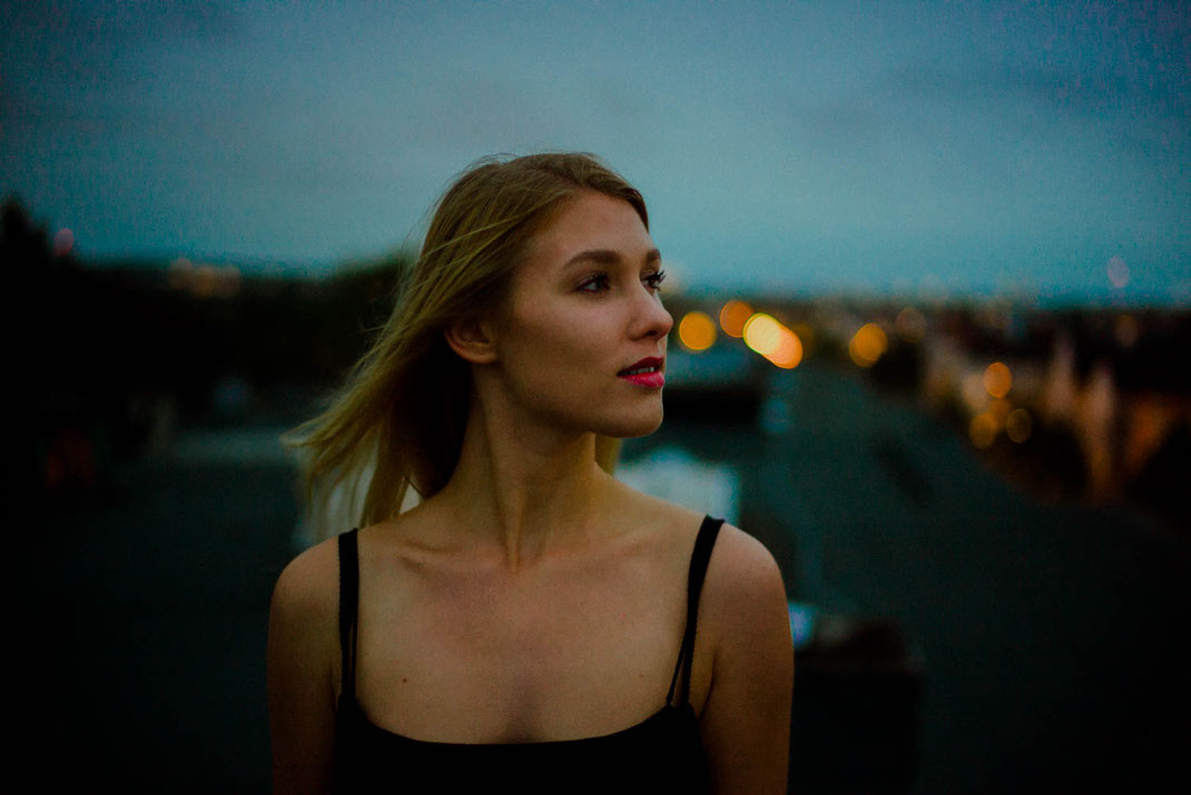 Frau blickt in die Ferne im Hintergrund die Lichter der Stadt