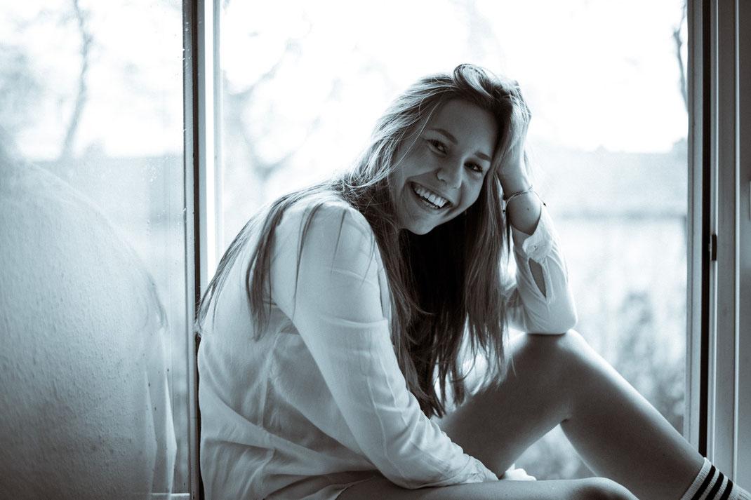 Junge Frau lacht herzhaft in die Kamera Fotoshooting Oldenburg