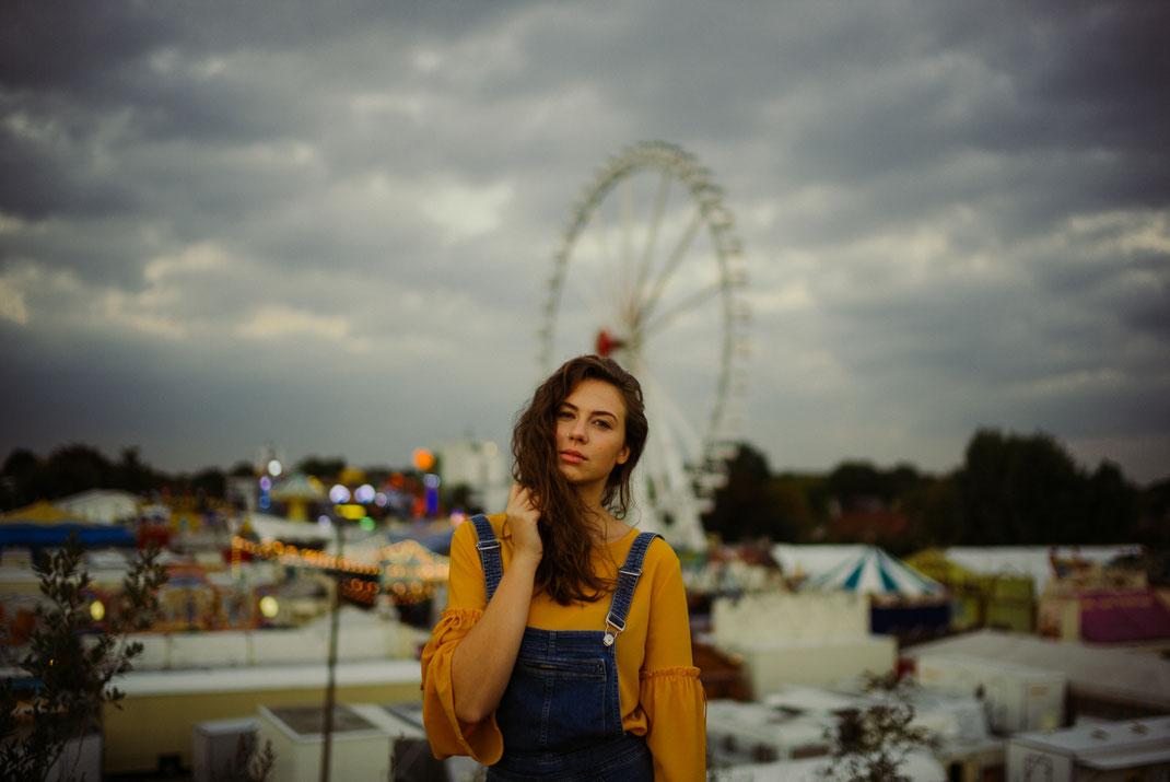 Junge Frau mit locken blickt in die Ferne im Hintergrund der Oldenburger Kramermarkt als Fotoshooting Location
