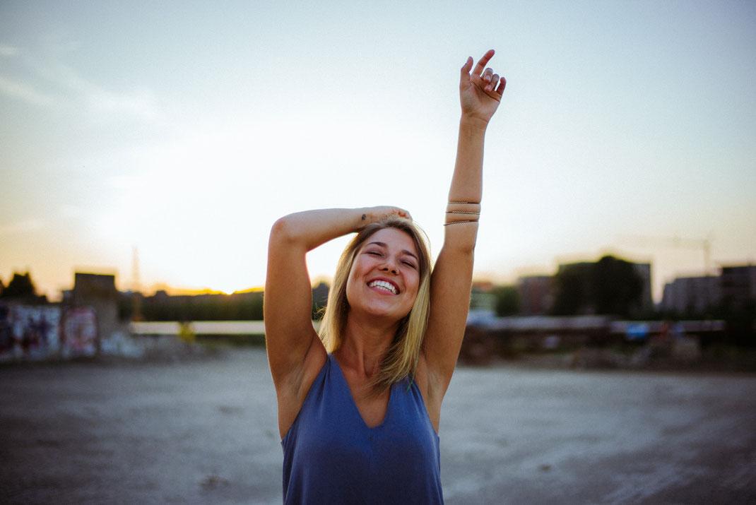 Frau streckt die Arme Richtung Himmel und lacht
