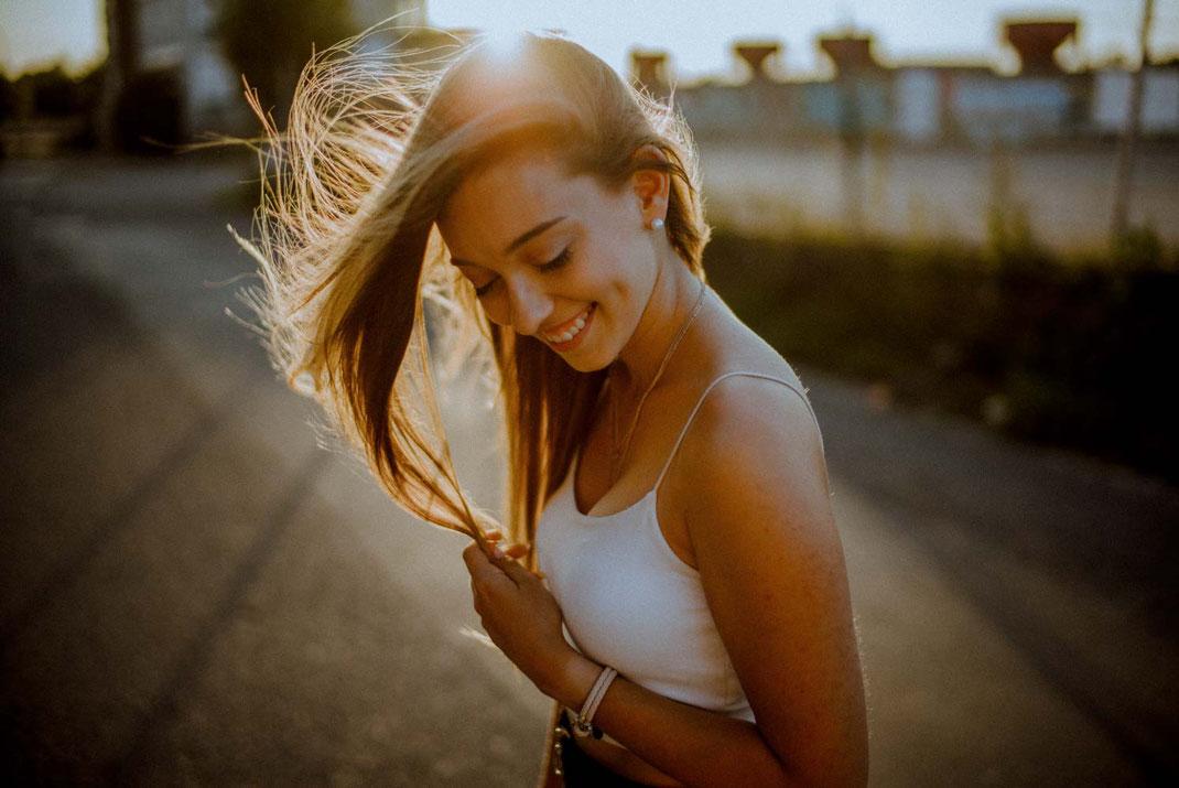Haare wirbeln im Gegenlicht durch die Luft