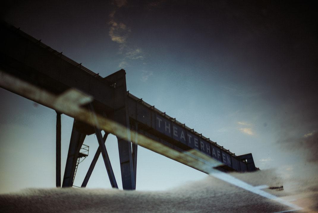 Spiegelung eines Hafenkranes in der Pfütze