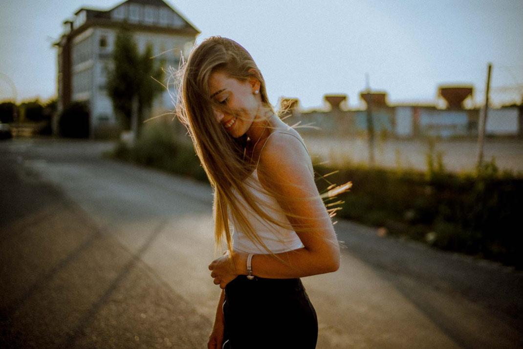 Wehende Haare einer lächelnden Frau im Gegenlicht am Oldenburger Hafen