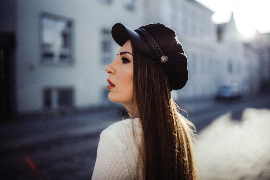 Frau mit Hut blickt die Straße entlang