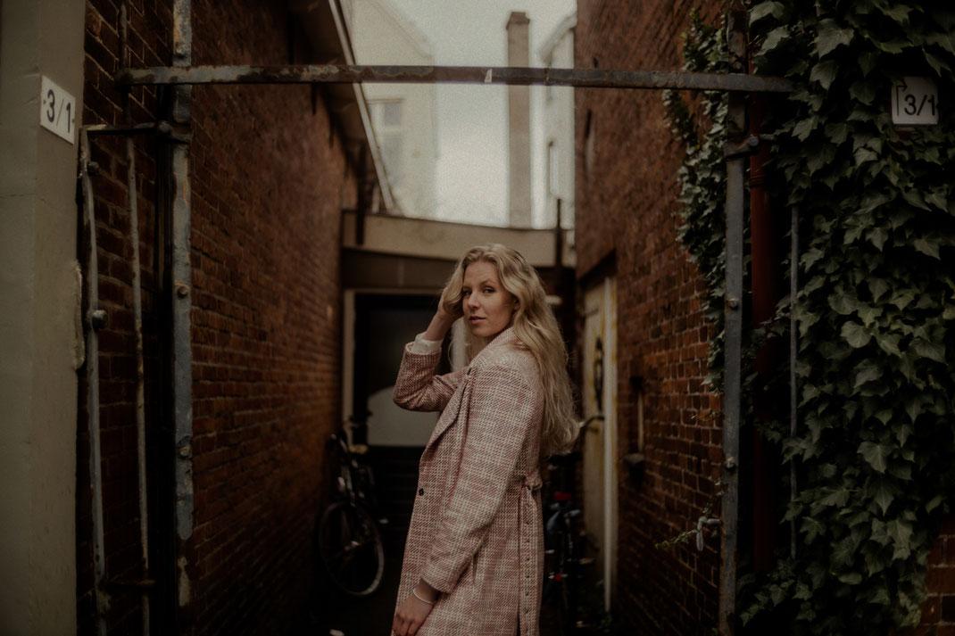 Model mit Mantel blickt in die Kamera
