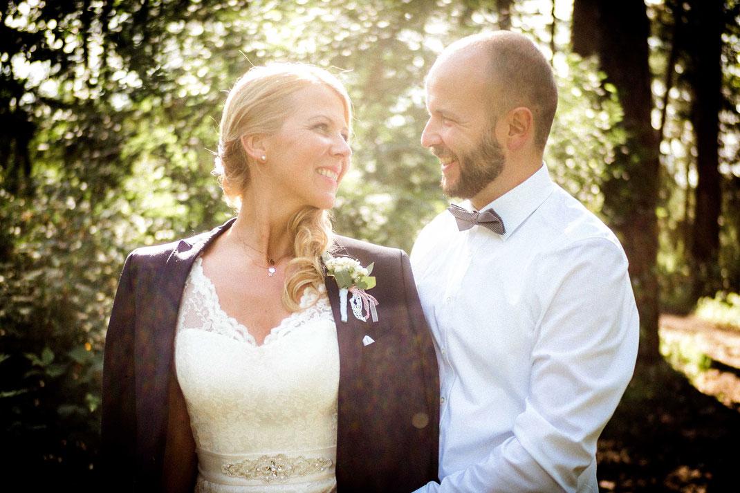 Frau mit Sakko lächelt ihren Mann an
