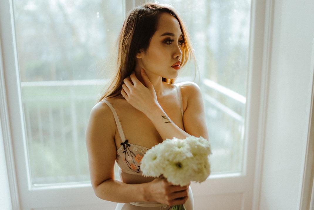 Frau in  Dessous mit Blumen in der Hand steht vor einem Fenster