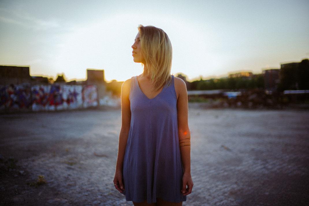 Frau mit Kleid schaut bei Sonnenschein in den Himmel