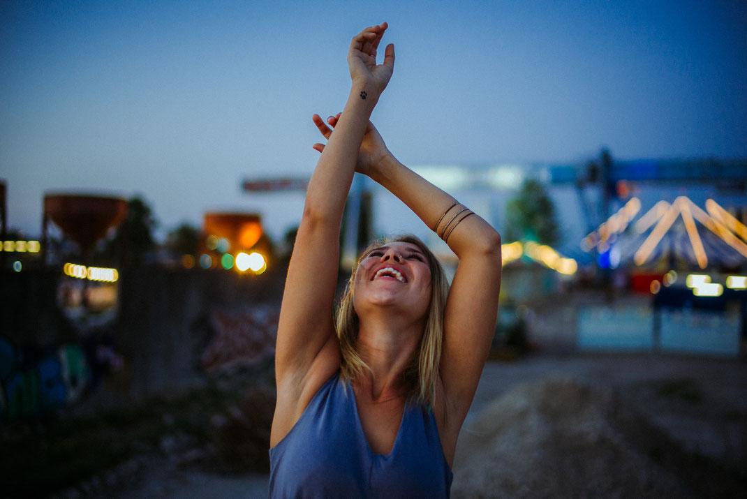 Frau lacht und streckt die Hände hoch
