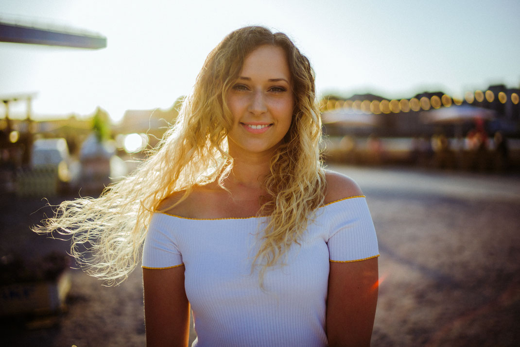 Junge Frau in sommerlichen Outfit blickt in die Kamera