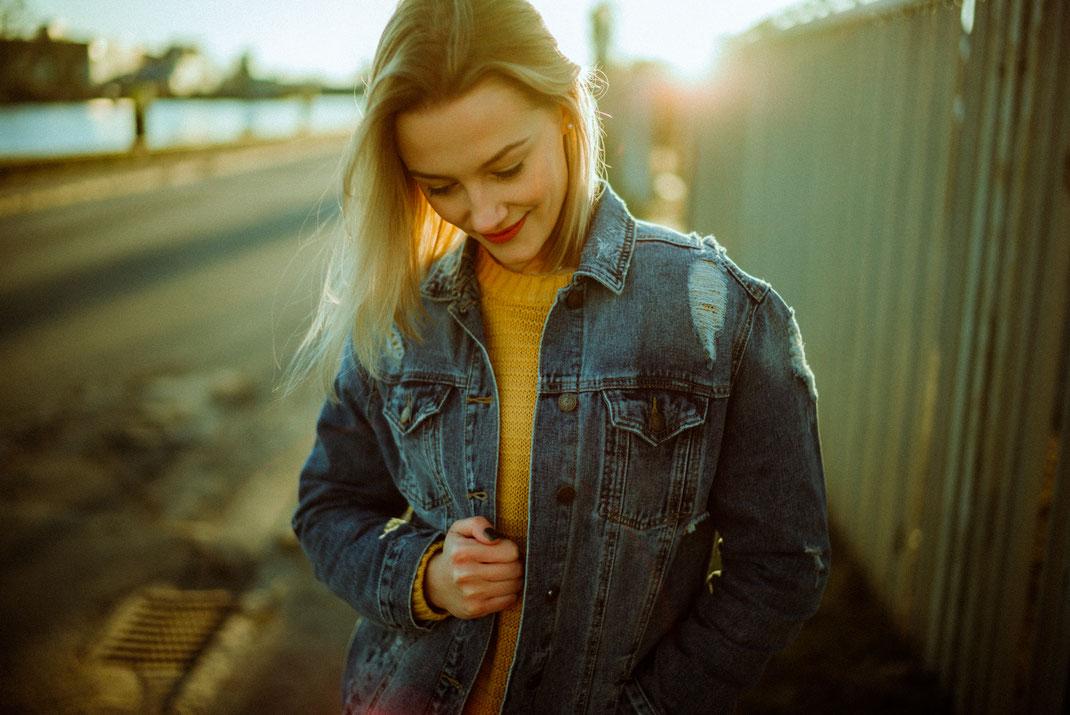 Junge Frau in Jeansjacke blickt nach unten