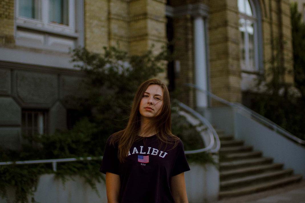 Junge Frau mit Print Shirt blickt in die Kamera im Hintergrund ein Gebäude mit Treppe