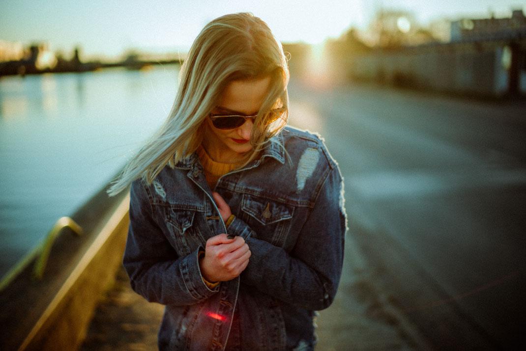 Frau mit Sonnenbrille klammert sich an ihre Jeansjacke