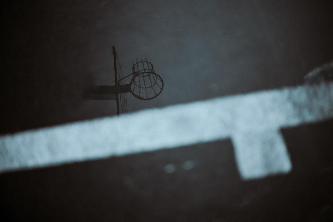 Spiegelung eines Basketballkorbes in einer Pfütze