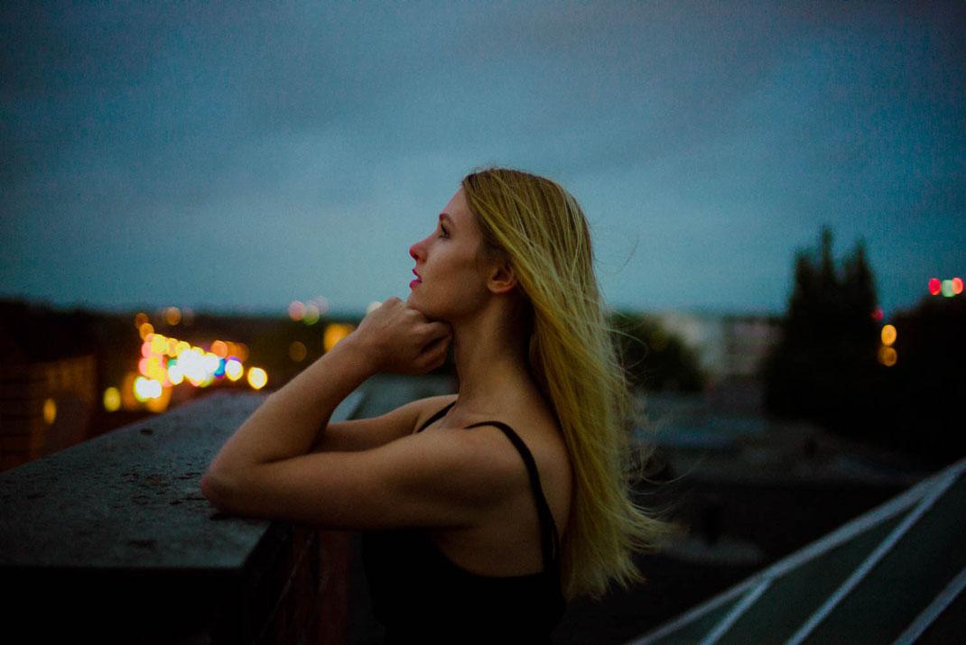 Frau blickt zur Seite im Hintergrund die Lichter der Stadt Hamburg