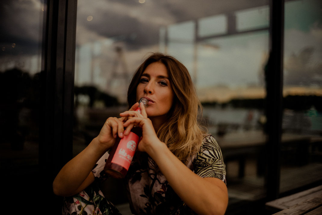 Junge Frau mit Fritz Getränk blickt in die Kamera