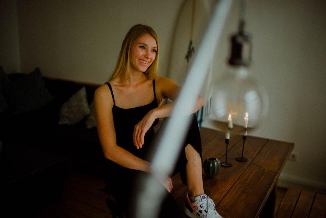 Junge Frau lächelt und sitzt auf dem Tisch