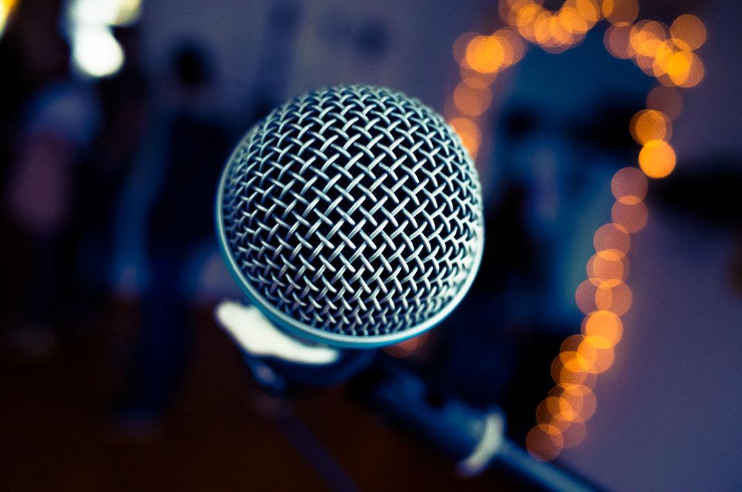 Mikrofon in Detailaufnahme im Hintergrund Lichterketten