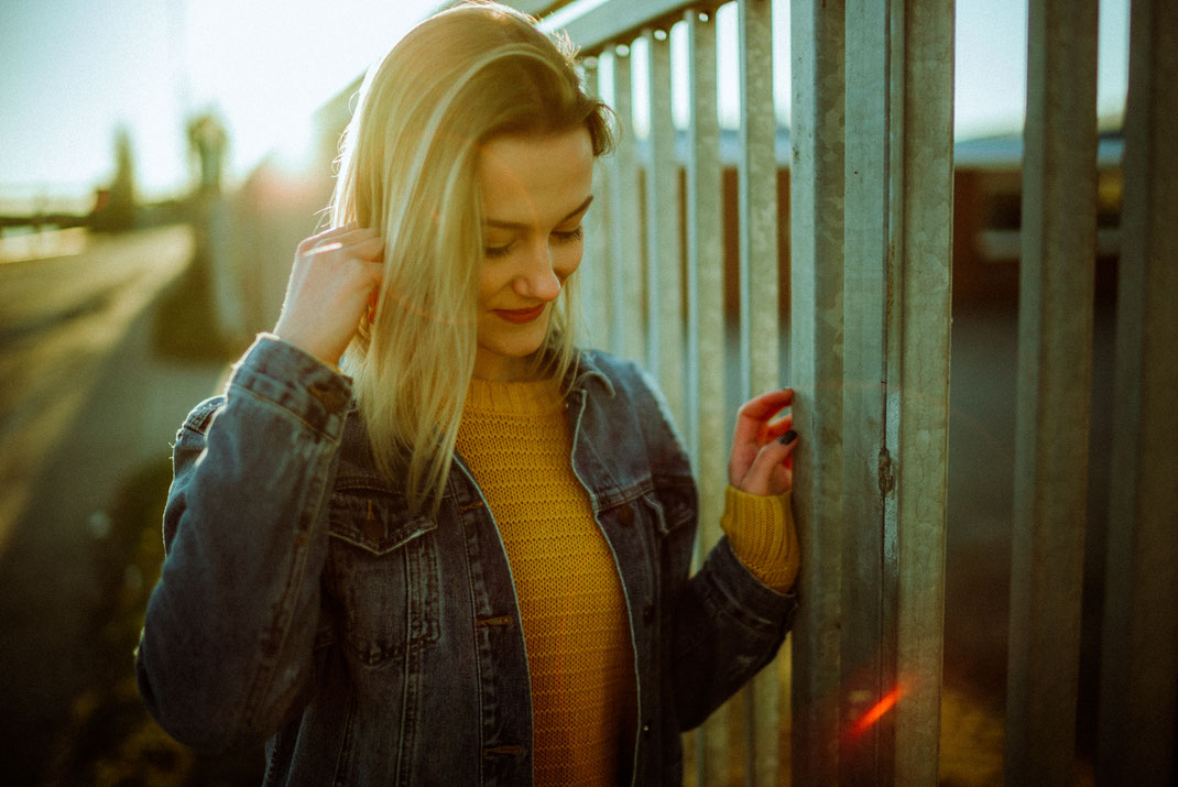 Junge Frau lehnt sich an einen Zaun