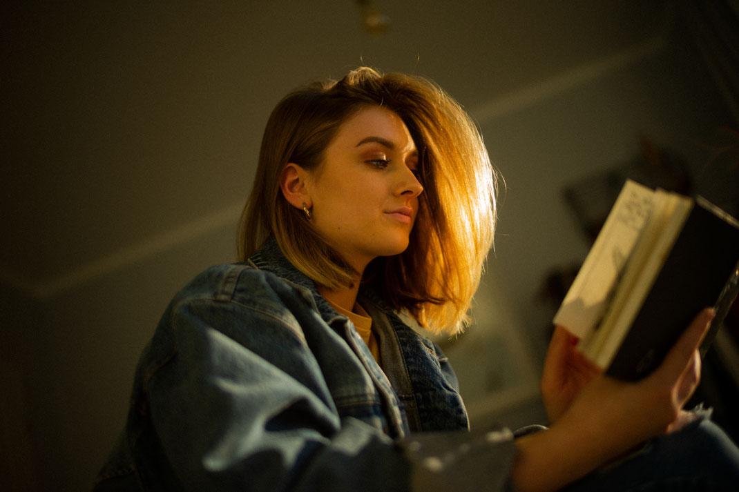Frau im Gegenlicht mit Buch in der Hand