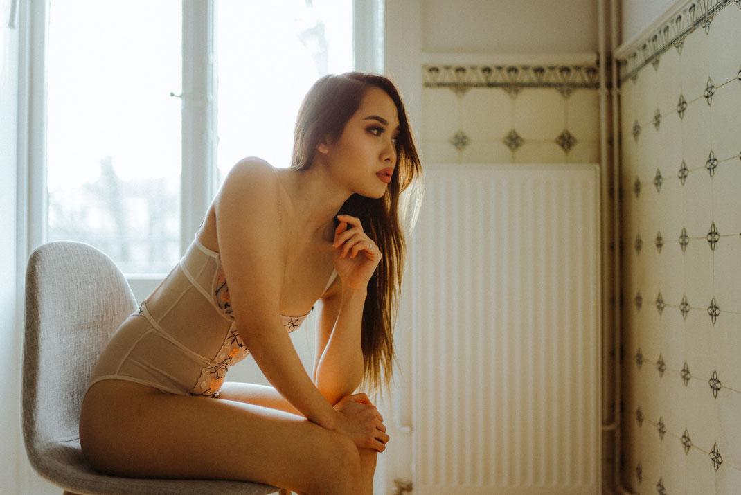 Frau in Dessous sitzt auf einem Stuhl und blickt Richtung Wand
