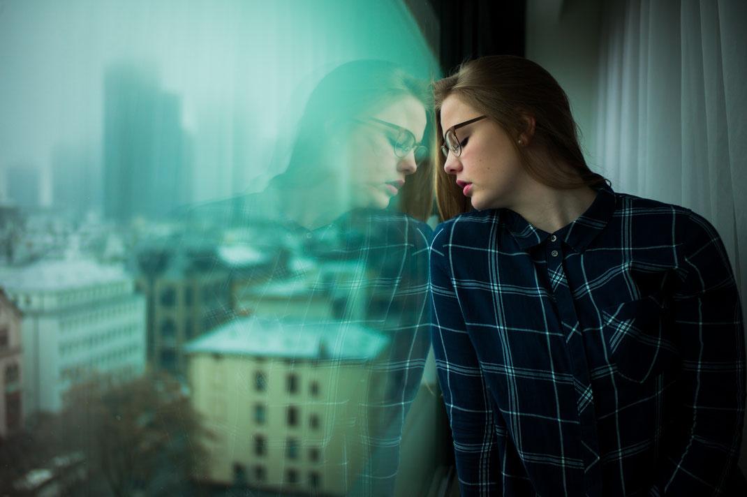 Spiegelung einer Frau in Glasscheibe eines Frankfurter Hotels