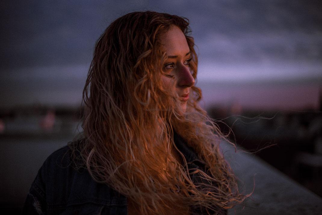 Frau schaut in die Ferne Haare wehen im Wind