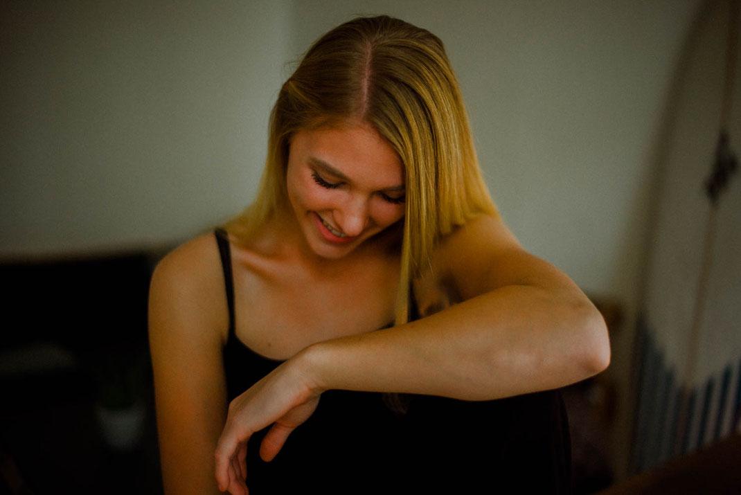 Junge Frau schaut nach unten und lächelt