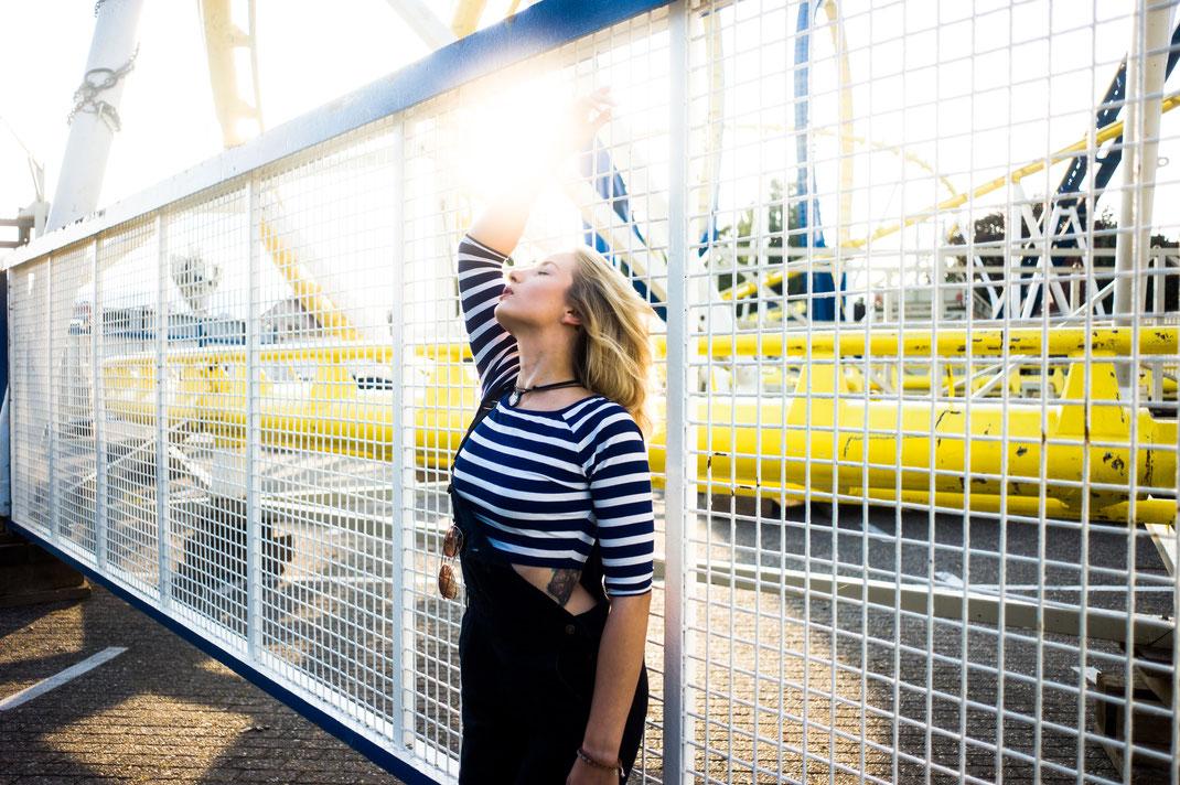 Styliche Frau lehnt am Zaun im Hintergrund Achterbahn mit Looping