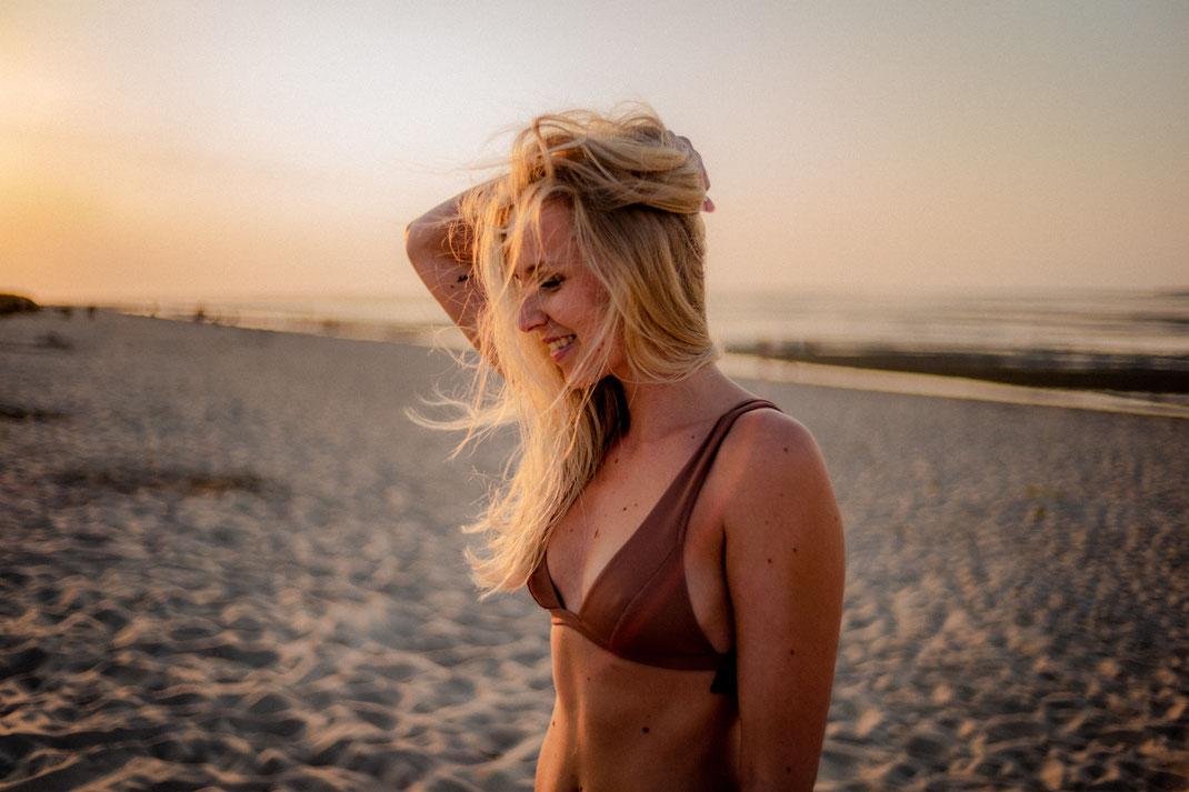Model mit wehenden Haaren am Strand