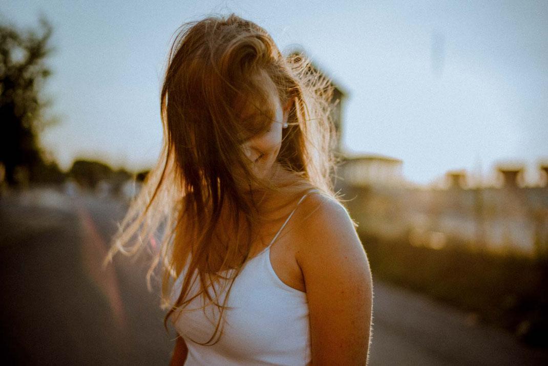 Junge Frau am Oldenburger Hafen die Haare verdecken das Gesicht