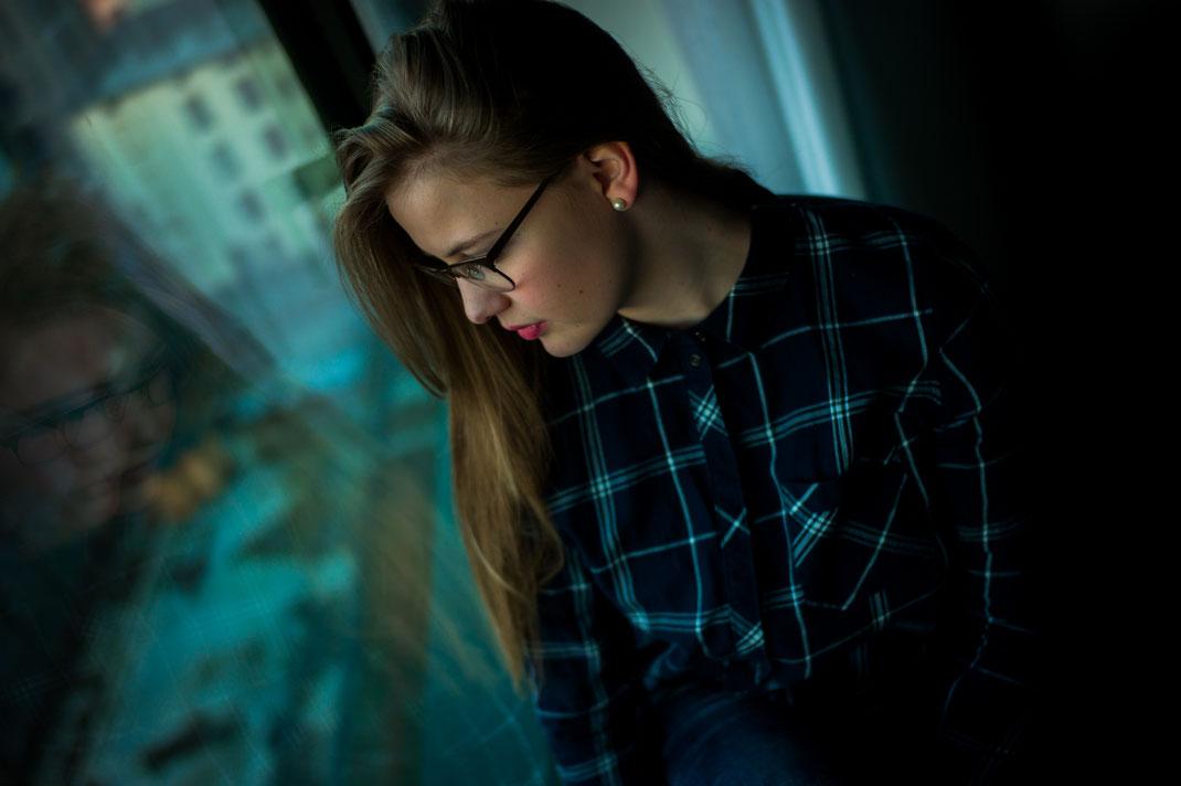 Frau schaut in Fensterscheibe eines Hotels und sieht ihre Spiegelung