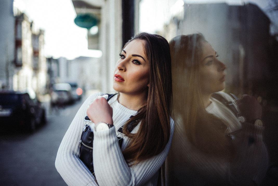 Junge Frau lehnt lässig mit dem Rücken an einer Fensterscheibe