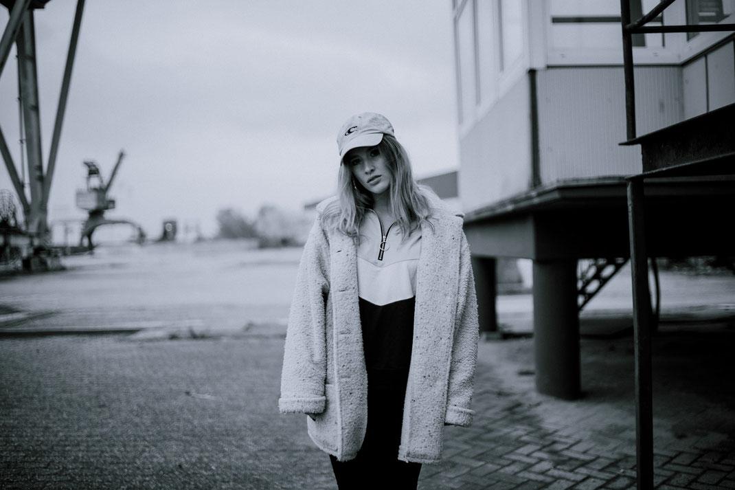 Junge Frau mit Mantel blickt in die Kamera Fotoshooting am Oldenburger Hafen