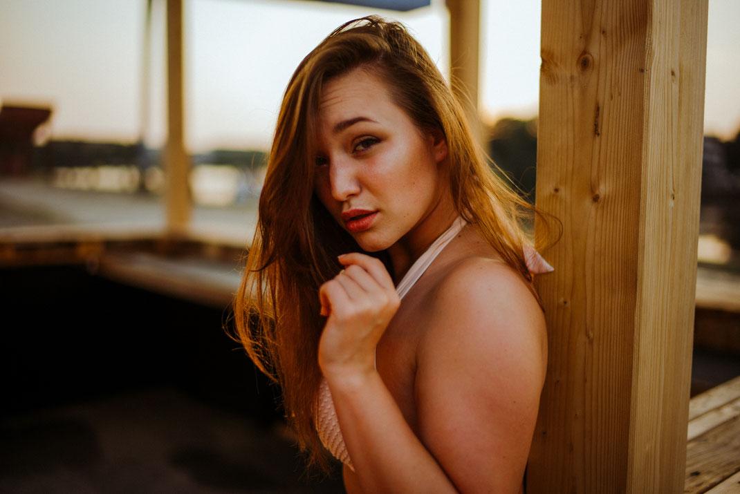 Frau blickt direkt in die Kamera und lehnt dabei an einem Holzbalken