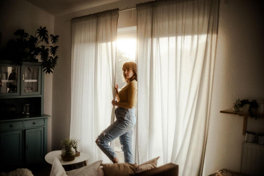 Junge Frau steht am Fenster Fotoshooting