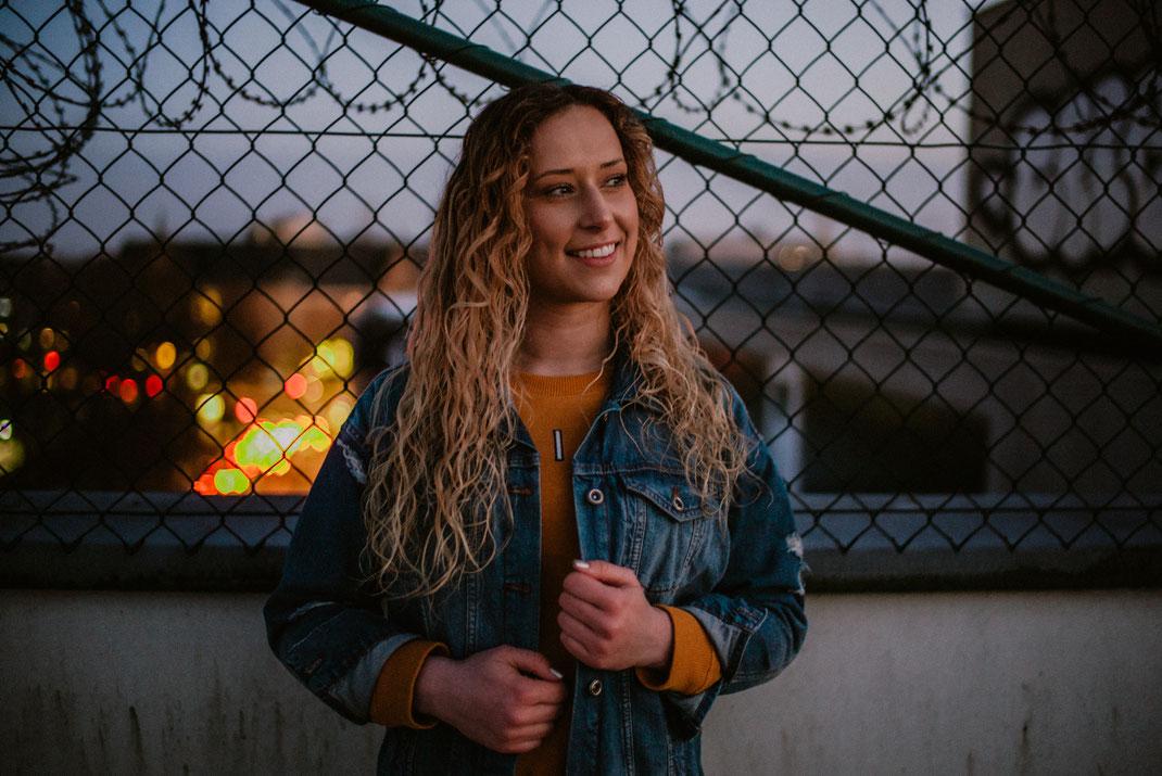 Lächelnde  Frau vor Zaun auf Dach