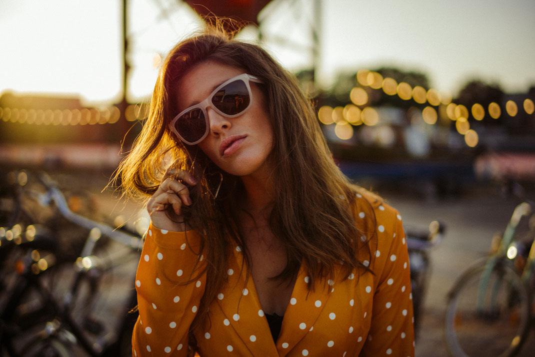 Frau mit Sonnenbrille blickt in die Kamera im Hintergrund Lichterketten