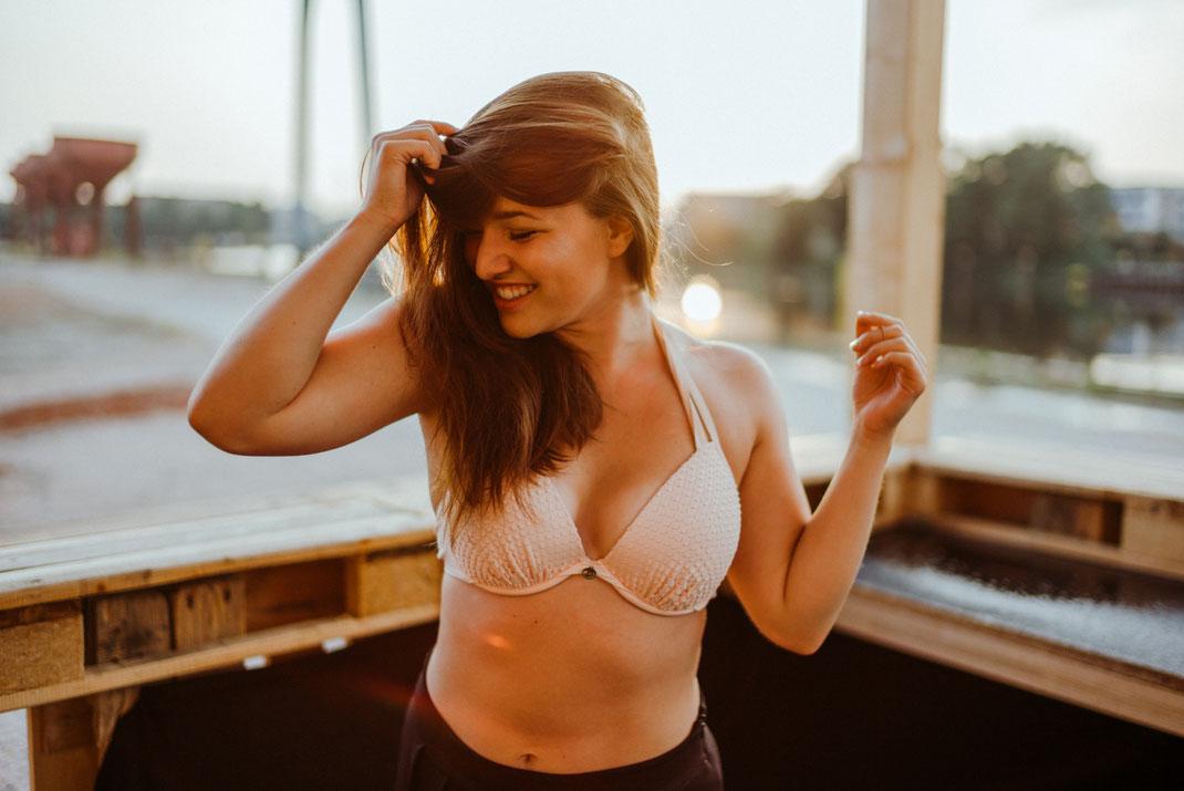 Junge Frau im Bikini lächelt und blickt zur Seite