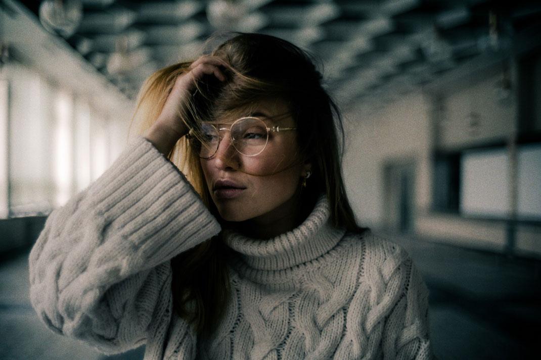 Model mit cooler runder Brille blickt Richtung Fenster