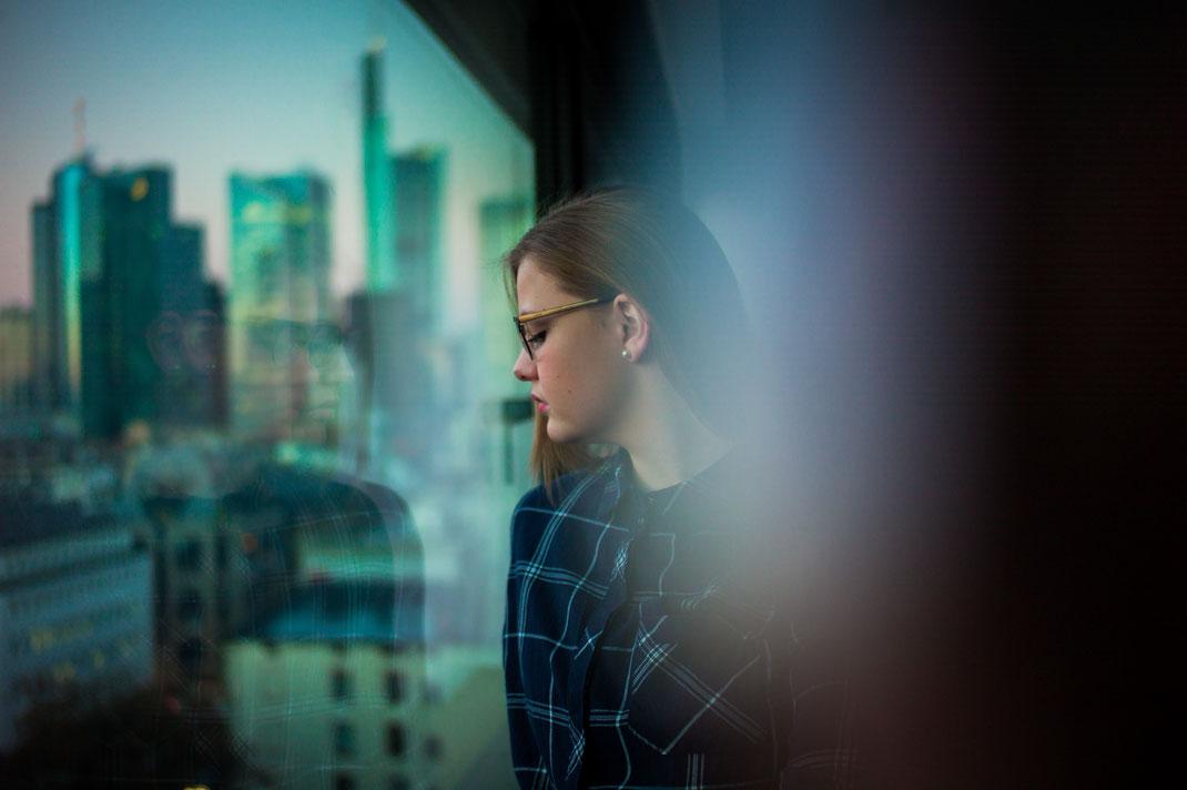 Junge Frau schaut aus Fenster im Hintergrund die Frankfurter Skyline