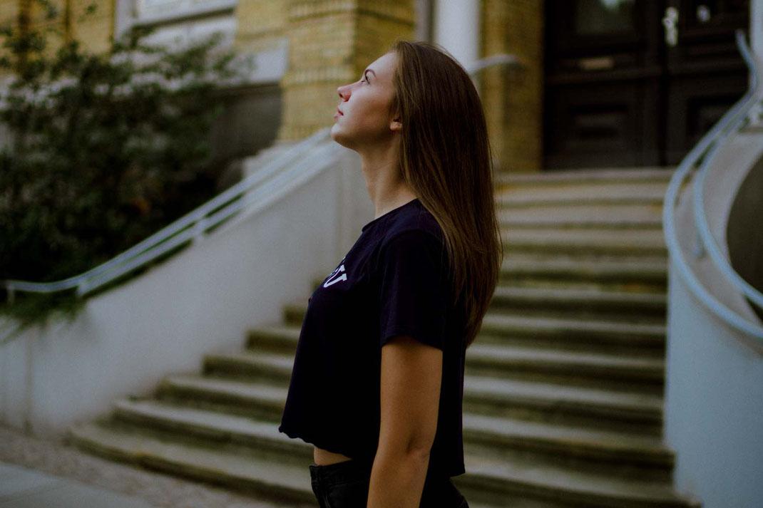 Frau mit bauchfreiem Outfit schaut in die Himmel im Hintergrund eine Treppe
