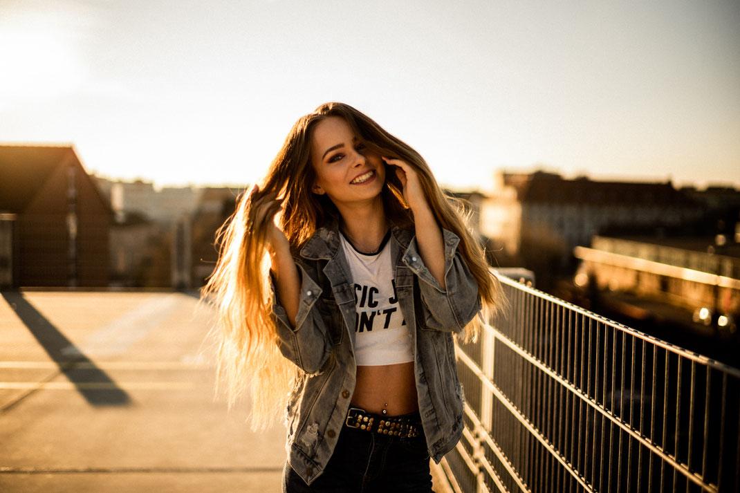 Junge Frau mit sommerlichem Outfit lächelt in die Kamera