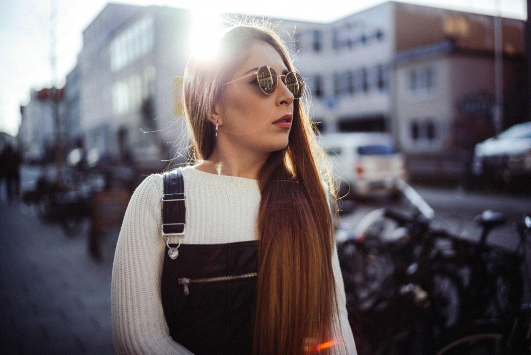 Junge Frau mit Latzhose und Sonnenbrille Gegenlicht und Lensflare