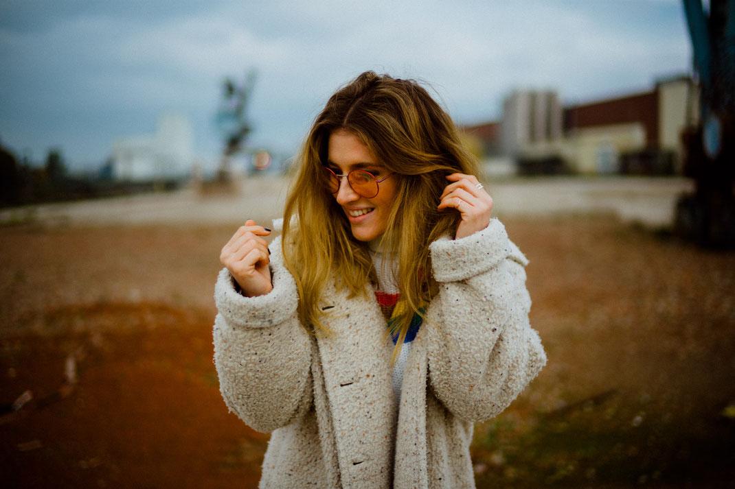 Lächelnde junge Frau mit Mantel und stylischer Sonnenbrille beim Fotoshooting