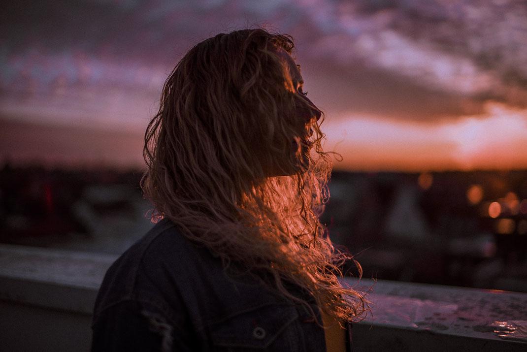 Haare bedecken das Gesicht einer jungen Frau Sonnenuntergang im Hintergrund
