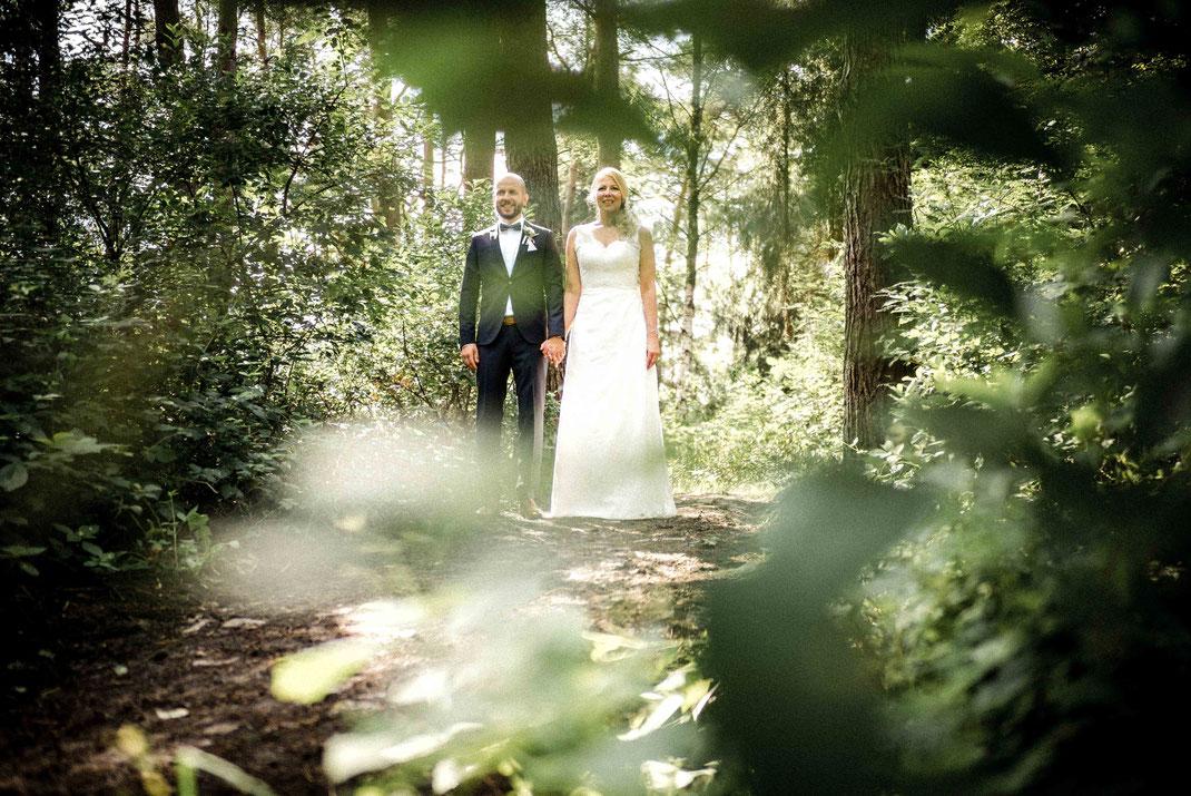 Brautpaar Hand an Hand im Wald im Bildvordergrund Bäume