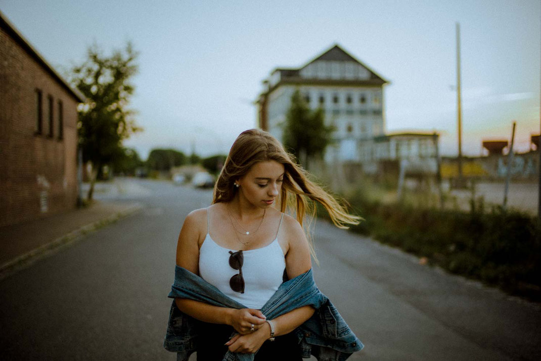 Frau mit Jeansjacke schaut nach unten im Hintergrund ein Gebäude