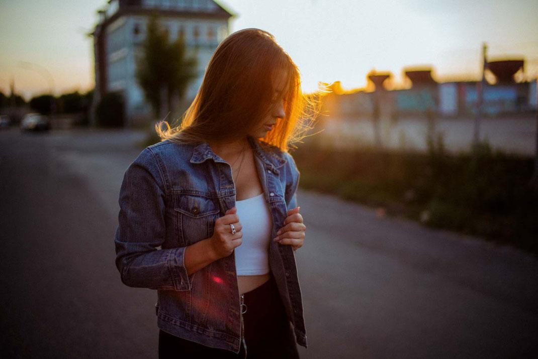 Junge Frau mit Jeansjacke im Gegenlicht