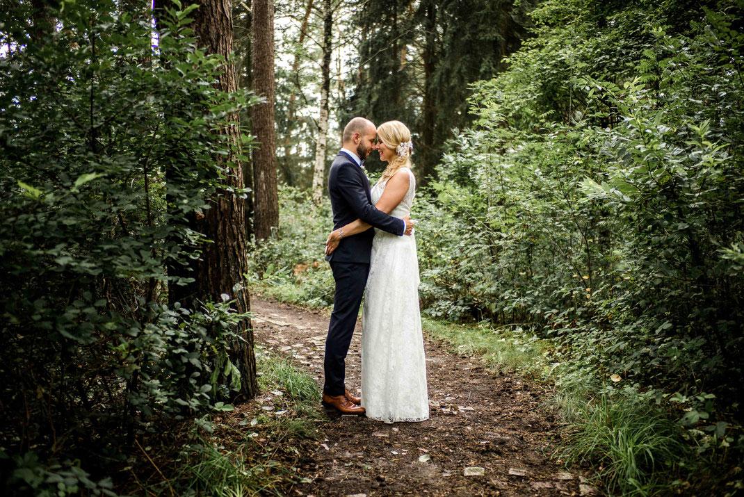Ganzkörperaufnahme des Brautpaares im Wald